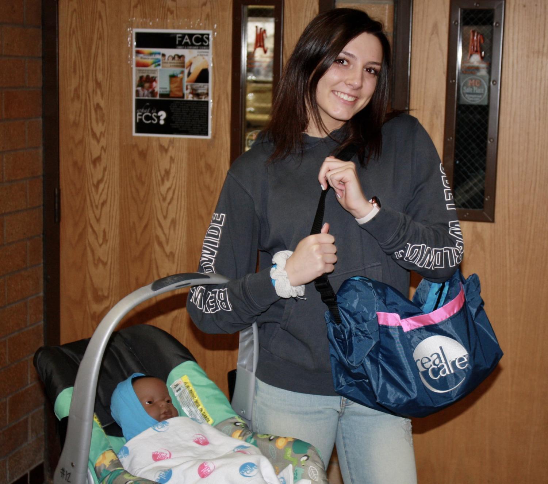 Sydney Wursten holding her baby. Photo by Saylor Funk.